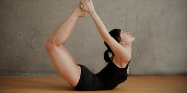 beautiful woman doing floor bow pose 1