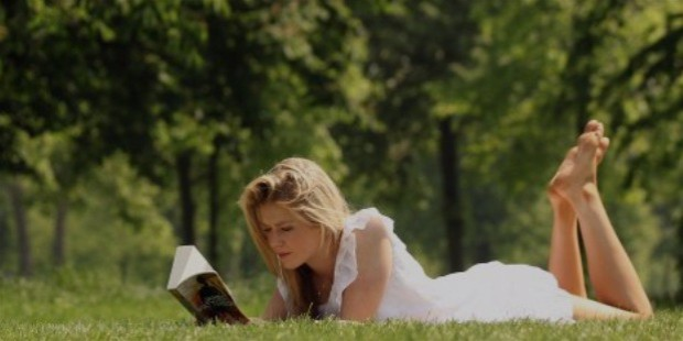 girl reading book field