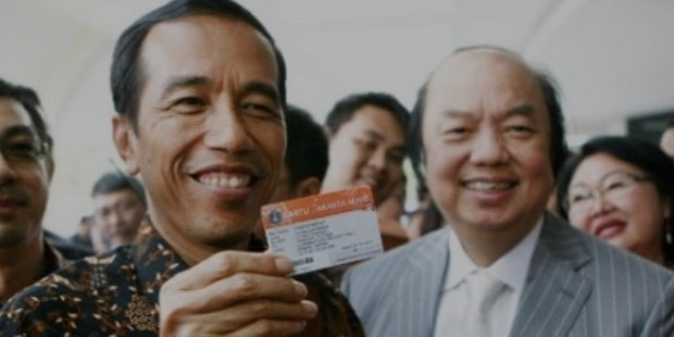 jokowi widodo  left  holds up a jakarta health card  kjs  besides mayapada group founder dato sri tahir
