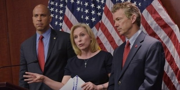 senator kirsten gillibrand, d ny, flanked by senator cory booker  l , d nj, and senator rand paul,