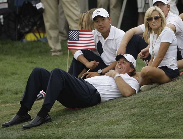 Phil Mickelson lies in front of his wife Amy