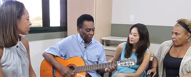 Pele playing guitar along with his wife and daughters