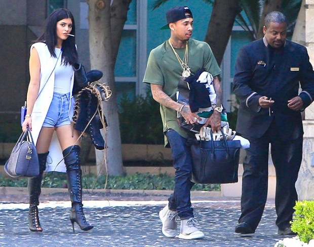 Kylie and Tyga holding their clothing