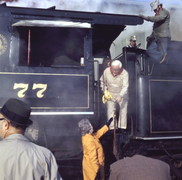 Colonel getting down from a train with help of his wife