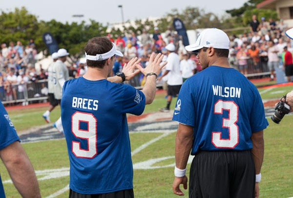 Drew Brees and Russell Wilson in a conversation during a match
