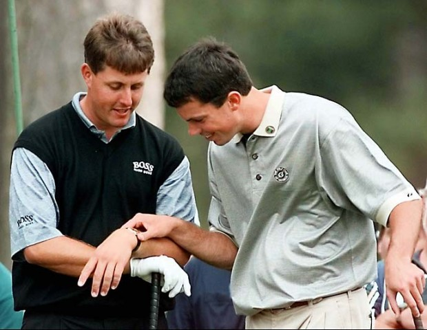 Matt Kuchar checks Phil Mickelson