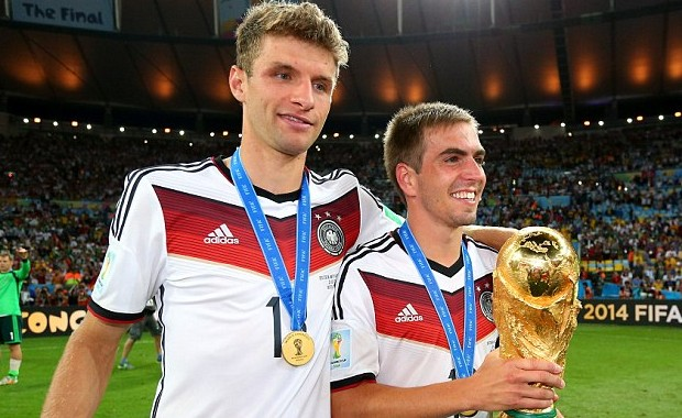Thomas Muller and Philipp Lahm celebrate with the World Cup