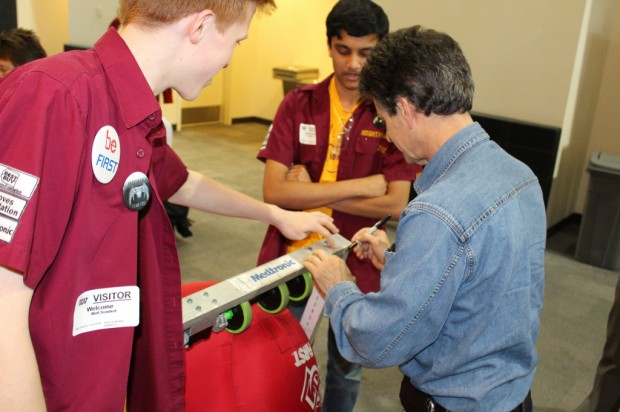 Dean Kamen signing his autograph on a robot that was made by students