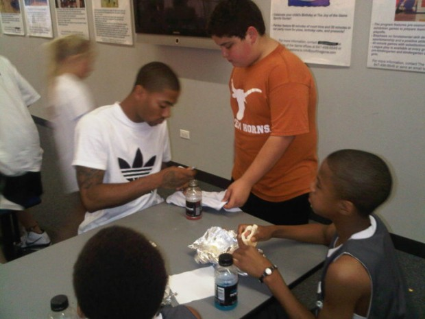 Derrick Signing Autographs to a Kid