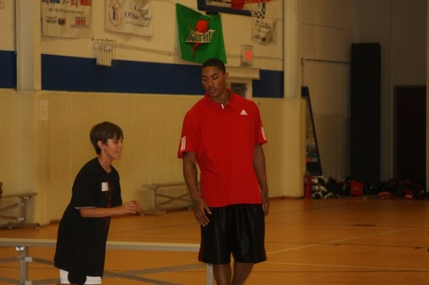 Derrick teaching a kid at Basketball Camp