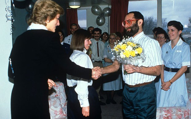 Princess Diana is presented with a bouquet of flowers by a patient at Mildmay Hospital