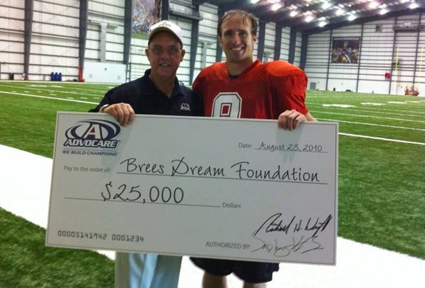 Drew Brees collecting a donation for his The Brees Dream Foundation