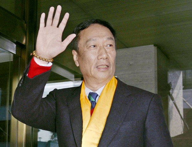 Terry Gou weaving his hand after arrival at Sharp Corp. headquarters building in Osaka
