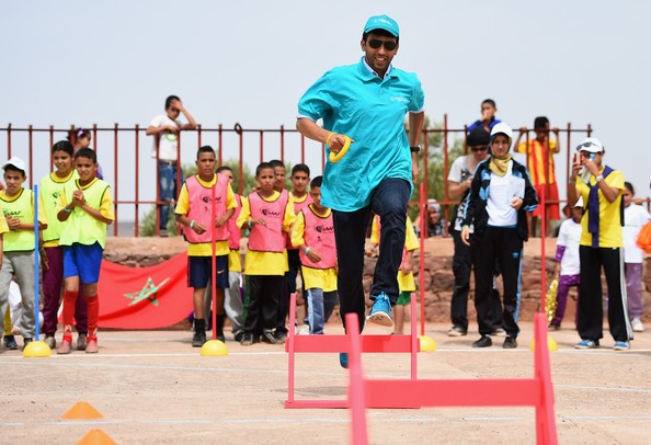 Long distance athlete Hicham El Guerrouj of Morocco takes part in the Kids Athletics session with local children at Ait Iktel