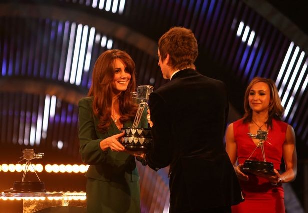 PA Bradley Wiggins accepts his award onstage from Kate Middleton