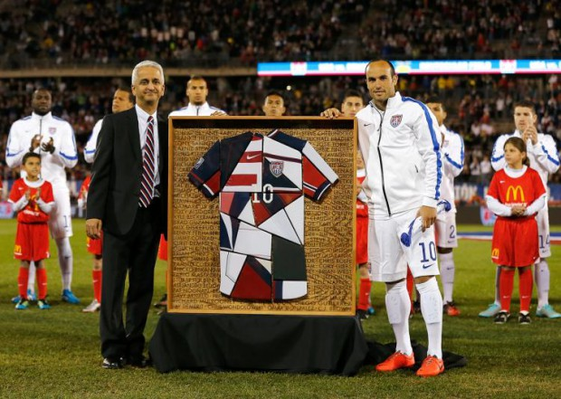 Landon Donovan is presented with a framed patch-quilt jersey by U.S. soccer boss Sunil