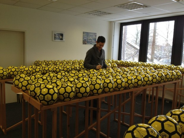 Lewy signing his autograph on footballs