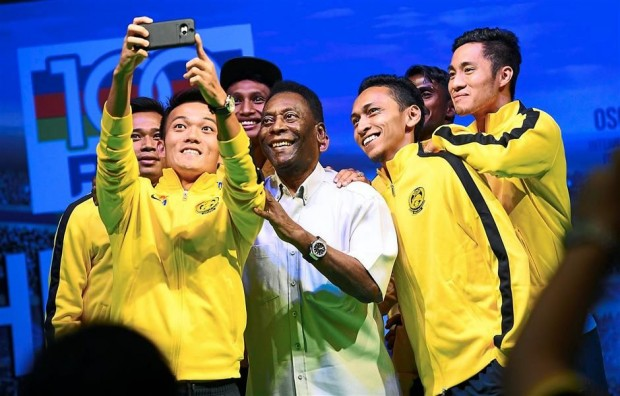 Pele posing for selfie with players from Harimau Malaya