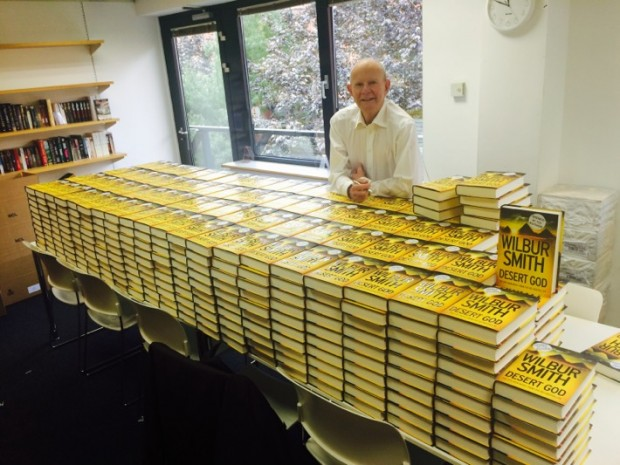 Wilbur Smith Posing With his Books