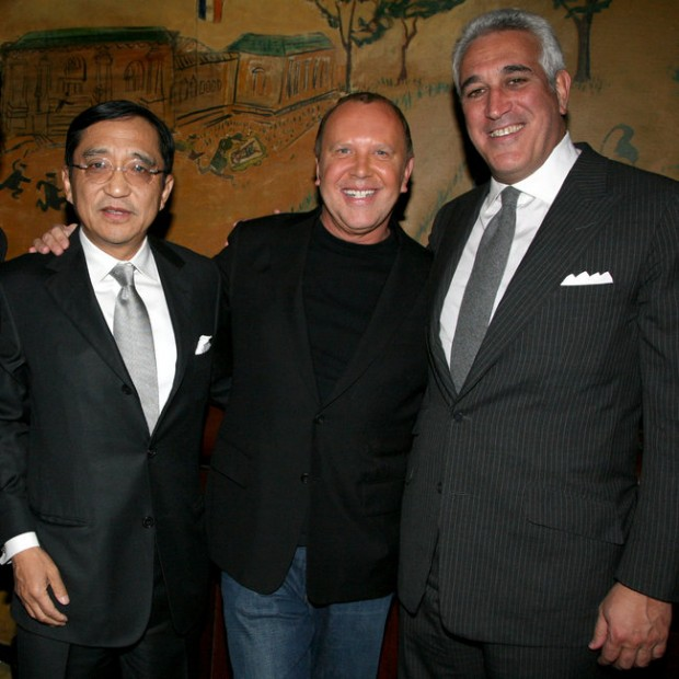 Silas K. F. Chou, left, and Lawrence S. Stroll, right, shown with the designer Michael Kors in 2011