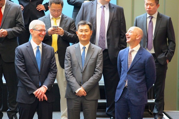 Apple CEO Tim Cook and Amazon CEO Jeff Bezos share a laugh