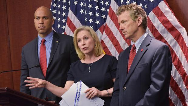 Senator Kirsten Gillibrand, D-NY, flanked by Senator Cory Booker (L), D-NJ, and Senator Rand Paul,