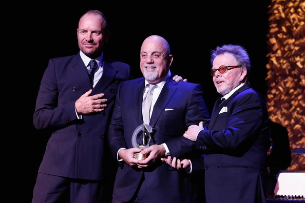 Billy Joel (C) receives an award onstage with Sting and Paul Wiliams at the ASCAP Centennial Awards