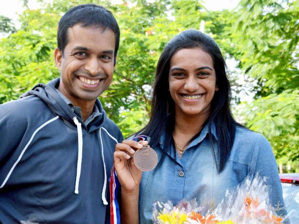 Sindhu showing her world championship medal along with her coach Gopichand