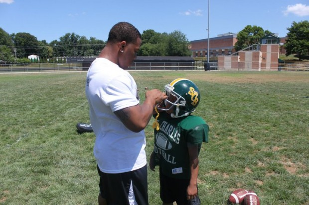 Ray Rice helping a kid with his helmet at Youth Football Camp