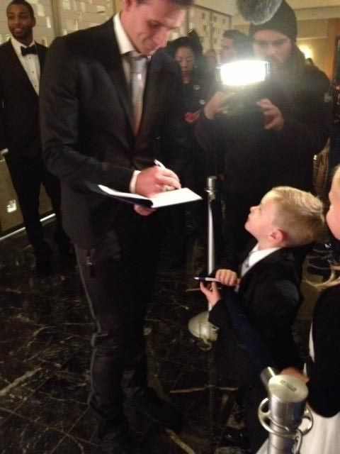 Ryan signing autograph to a kid fan at The Golden Goggle Awards
