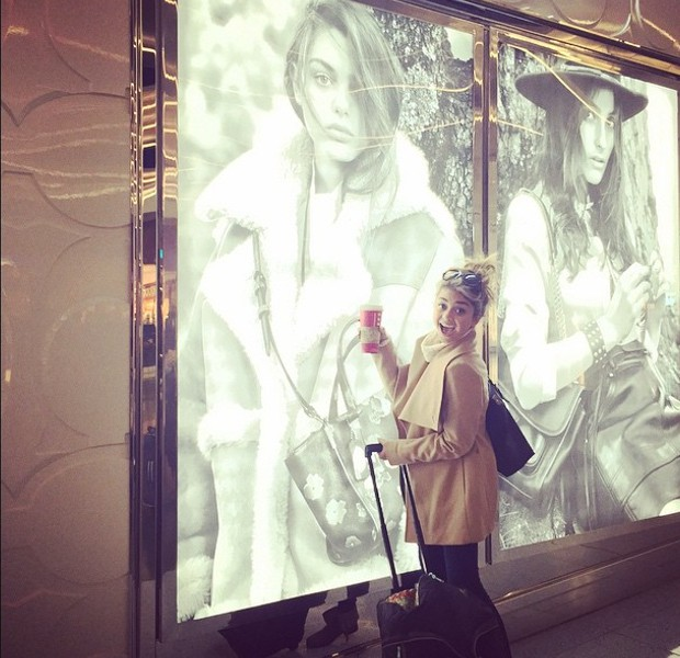 Sarah Hyland standing infront of Odeya Rush picture at an airport