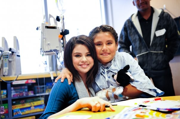 Selena with a kid at Dallas Children Hospital
