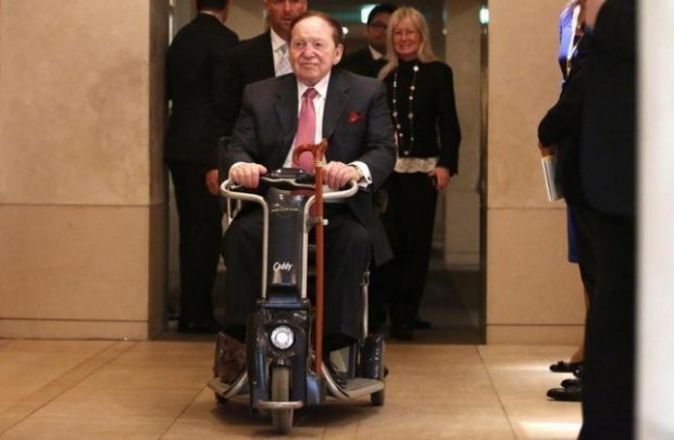 Sheldon Adelson rides his wheelchair after a news conference in Tokyo