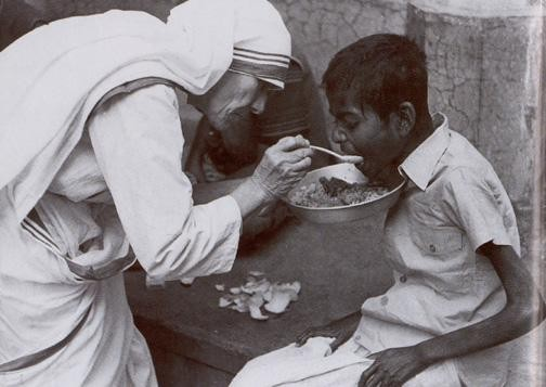 Mother Teresa feeding food to a kid