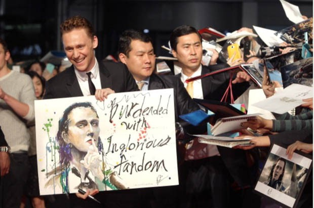 Tom showing a painting of him made by his fan